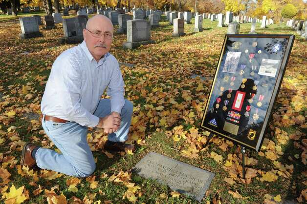 Mark Bodnar, nephew of Joseph J. Kucskar, a WWII soldier who walked the Bataan Death March and died in the Philippines in 1943, has worked for 25 years to recognize his uncle's sacrifices. He poses near his uncle's third grave, bringing historic photos and documentation at St Agnes Cemetery on Thursday Nov. 5, 2015 in Menands, N.Y.  (Michael P. Farrell/Times Union) Photo: Michael P. Farrell / 00034093A