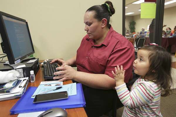 Angela Baker, with daughter Mary Jane Martinez helping,  scans the range of insurance options available to her as the San Antonio Eastside Promise Zone offers a Promise Zone to Health event with free health screenings for residents and their children on November 5, 2015.  Baker, a working single mom, was seeking an affordable way to cover her family and first stepped into the marketing assistance room at the fair.