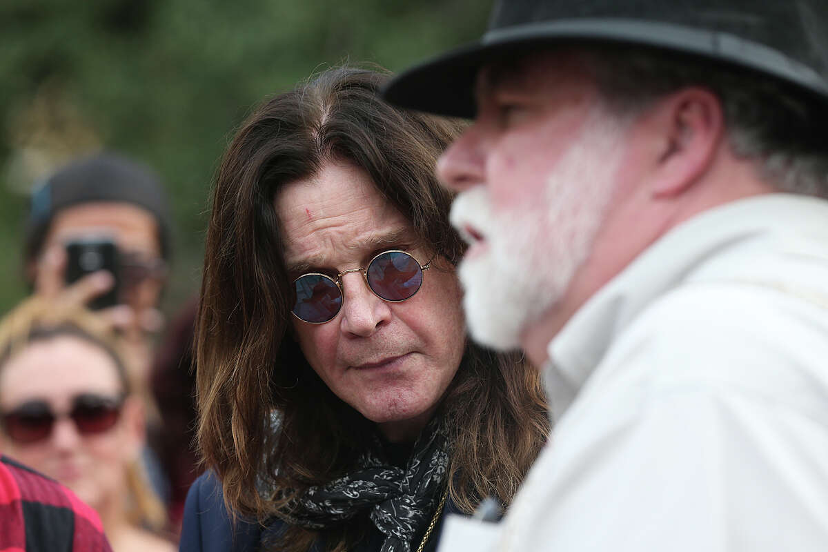 Rocker Ozzy Osbourne, left, listens to historian and author Stephen L. Hardin, as he arrives at the Alamo.