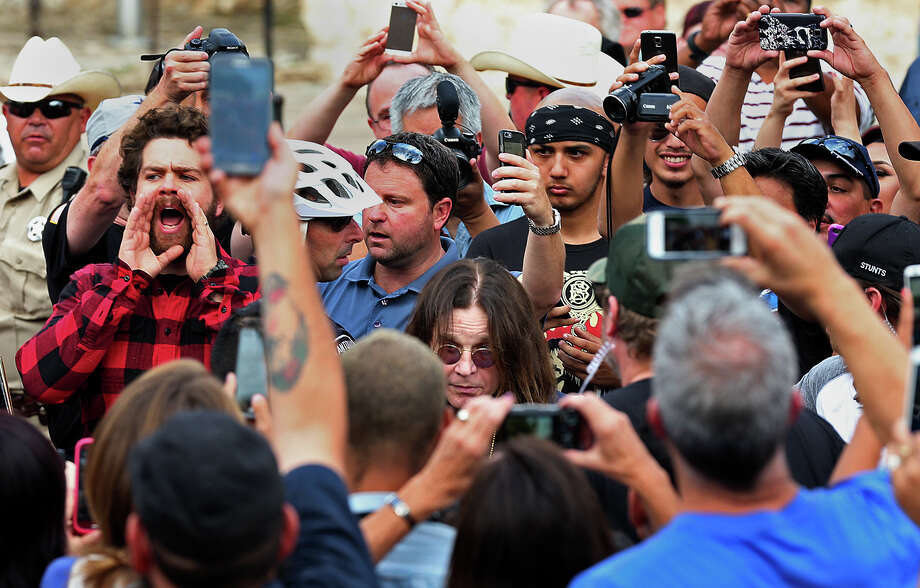 Fans and media surround Ozzy Osbourne (center) as he arrives at the Alamo. Osbourne, who was arrested in 1982 for urinating on the Alamo Cenotaph, is filming a show for the History Channel with his son, Jack (left, shouting). Photo: Jerry Lara /San Antonio Express-News / © 2015 San Antonio Express-News