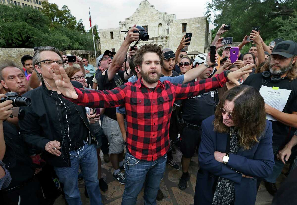 Jack Osbourne (center) tries to calm the crowd as he and his father Ozzy Osbourne (right) arrive at the Alamo.