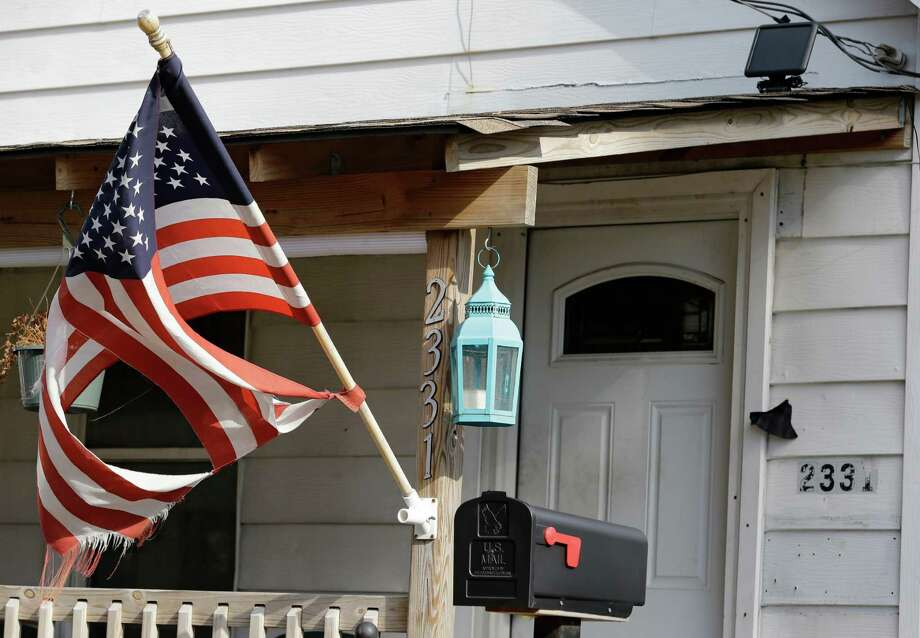 A tattered flag flies Thursday in front of a Cleveland home where Julian Hernandez lived with his father, Bobby Hernandez. Thirteen years after Julian was allegedly snatched from his Alabama home at age 5 by his father, he has been found living under an assumed name with his dad in Ohio. Photo: Tony Dejak, STF / AP