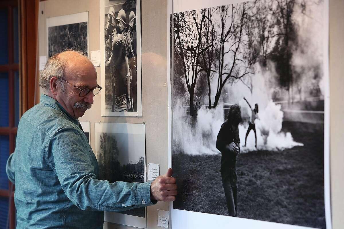 Photojournalist Ken Light arranges a display case to better photograph his work at UC Berkeley in Berkeley, Calif., on Thursday, November 5, 2015.