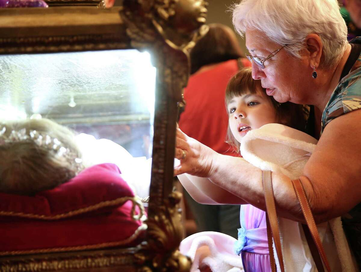 """Attendees touch the reliquary holding the relics of St. Maria Goretti on display at Catholic Charismatic Center on Thursday, Nov. 5, 2015, in Houston. Known as the """"little saint with great mercy"""" St. Maria Goretti's relics are touring the U.S. to bring Pope Francis' message for the year of Mercy."""
