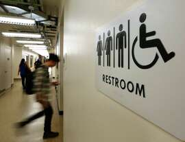 Students pass by a sign for a unisex bathroom next to the men's and women's restroom at the University of Houston Downtown, Thursday, Nov. 5, 2015, in Houston.