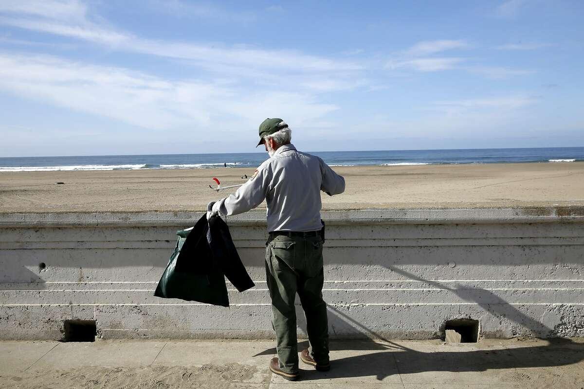 Maintenance worker James Brown picks up trash at Ocean Beach in San Francisco, California, on Thursday, Nov. 5, 2015.