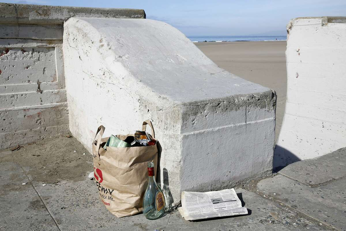 A bag of trash, a newspaper and an empty glass bottle on the ground near stairwell 13 at Ocean Beach in San Francisco, California, on Thursday, Nov. 5, 2015.