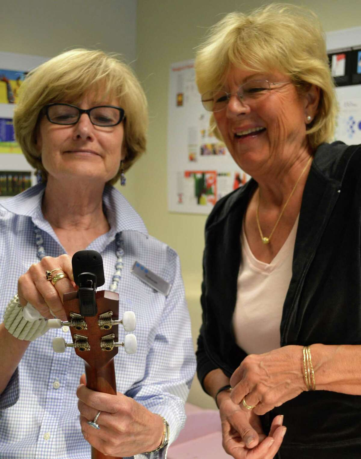 Deborah White, left, who organized the Ukelele Meetup at the library, helps Dolores Noble Steadly, of Westport, tune up.