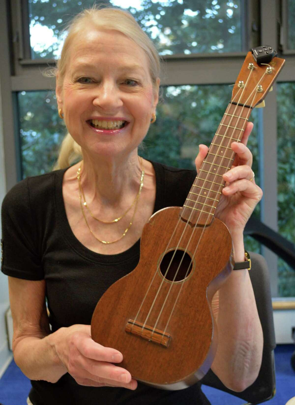 Pat Blaufuss, of Westport, shows off the 60-year-old Martin ukelele she inherited from her mother.