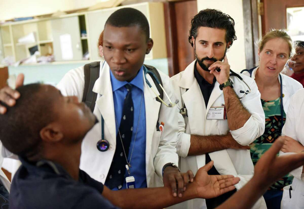 Intern Dr. Alex Kayongo, left, examines a patient as Dr. Sohi Ashraf, of Norwalk, Conn., and University of Vermont first-year medical student Alexandra Miller watch during clinical rounds at Mulago Hospital in the capital city of Kampala, Uganda.
