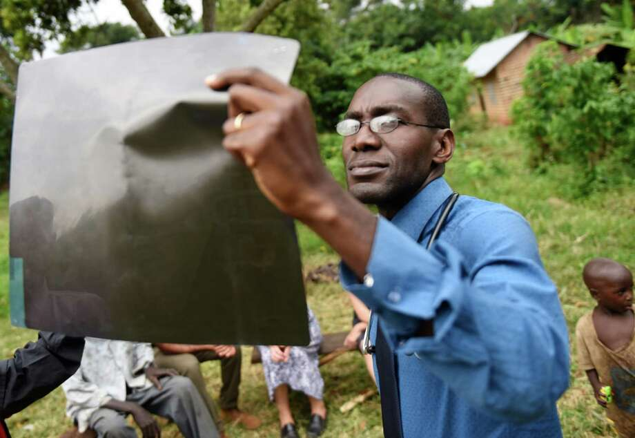 Dr. Robert Kalyesubula looks at an HIV positive patient's X-ray during an ACCESS Health Training Institute home visit in the rural town of Nakaseke, Uganda. Photo: Tyler Sizemore / Hearst Connecticut Media / Greenwich Time