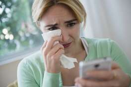 Crying Caucasian woman using cell phone