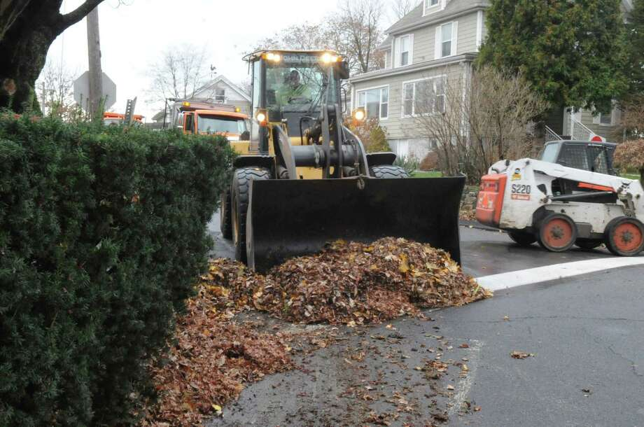 Chris Sandor, of the Greenwich Department of Public Works collects leaves on Valley Road in 2011. Leaf collection begins again in Greenwich on Monday, weather permitting. Photo: Helen Neafsey / Helen Neafsey / Greenwich Time