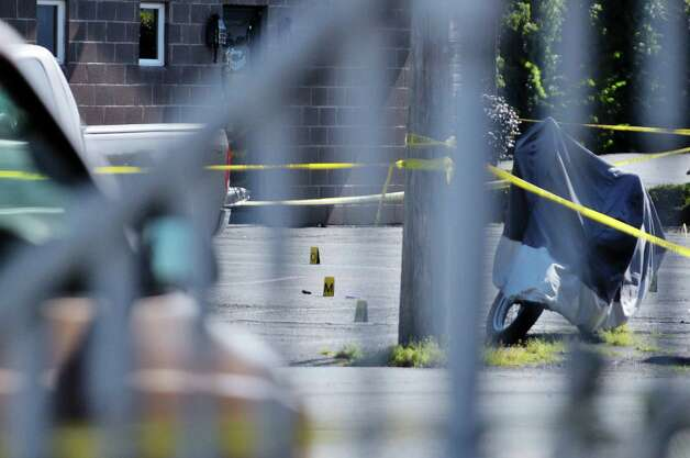Evidence cards are seen on the ground in a parking lot at the corner of 112th St. and East Park Place, as Troy Police work at the scene where two officers were shot Saturday night, on Sunday, Aug. 23, 2015, in Troy, N.Y.    (Paul Buckowski / Times Union)