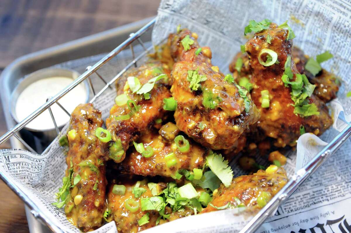 Curry Wings with coconut curry, toasted peanuts, cilantro and scallions on Friday, Oct. 30, 2015, at Crave in Albany, N.Y. (Cindy Schultz / Times Union)