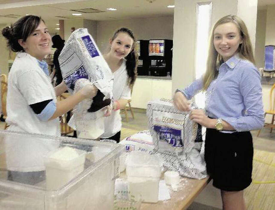 Lexi Kelley, center, the founder of Kids Helping Kids in Stamford, is shown in this file photo during the organization's annual bread bake fundraiser. Kelley is in college this year, but the event will continue on. Photo: Contributed Photo / Contributed Photo / New Canaan News