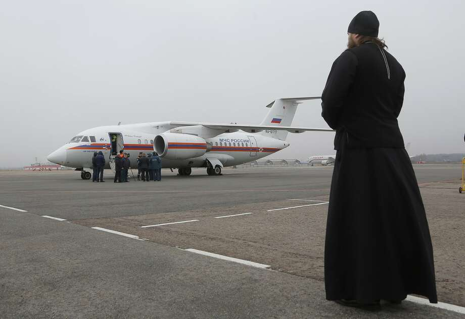 An Orthodox priest in St. Petersburg looks on as a plane arrives with the bodies of victims of the passenger jet that crashed en route from Sharm el-Sheikh, Egypt, to St. Petersburg, Russia. Photo: Dmitry Lovetsky, Associated Press