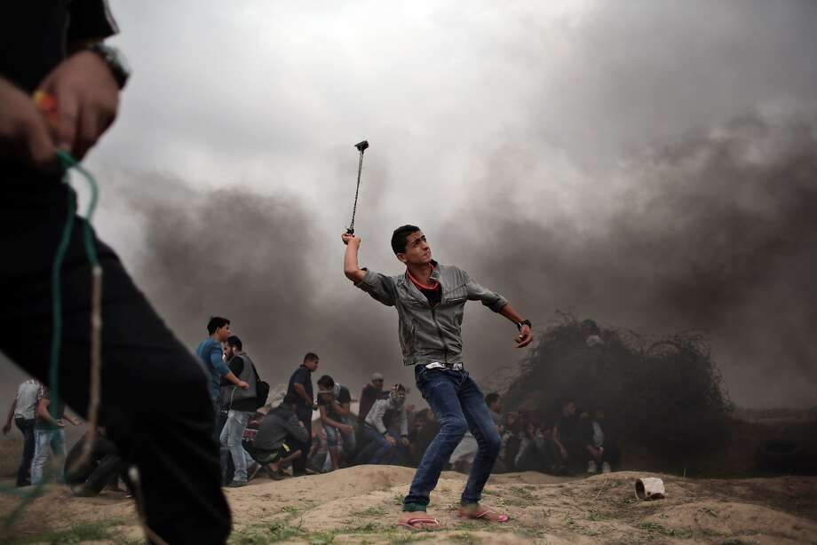 A Palestinian protester hurls stones using a sling shot during clashes with Israeli soldiers on the Israeli border with Gaza in Bureij, central Gaza Strip, Friday, Nov. 6, 2015. (AP Photo/ Khalil Hamra) Photo: Khalil Hamra, Associated Press