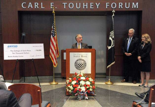 Ronald Romano, center, president and CEO NYSID, donates a check for $10,000 for a Battle Buddy Center during a dedication ceremony for The College of Saint Rose Veteran Center on Friday Nov. 6, 2015 in Albany, N.Y.  (Michael P. Farrell/Times Union) Photo: Michael P. Farrell / 00034082A