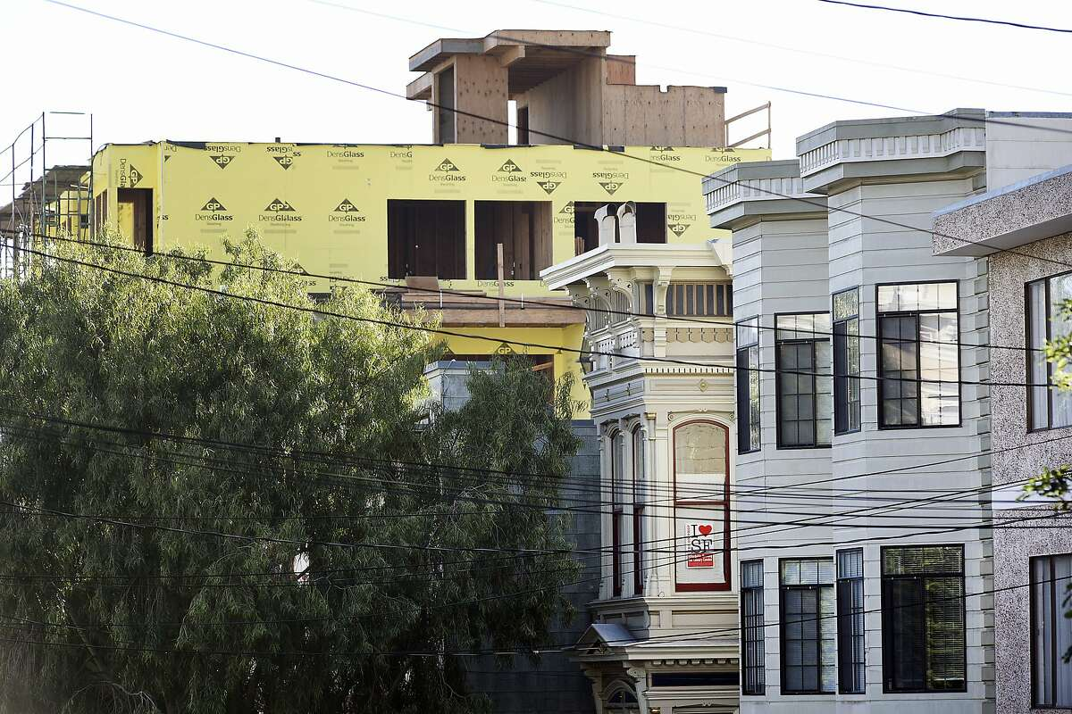 A pro-affordable housing poster hangs in a window as construction of new housing developments loom in the Mission District of San Francisco in November, 2015.