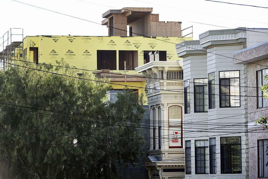 A pro-affordable housing poster hangs in a window as construction of new housing developments loom in the Mission District of San Francisco in November, 2015. Photo: Michael Short, Special To The Chronicle