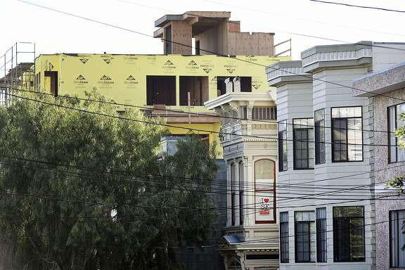 A pro-affordable housing poster hangs in a window as construction of new housing developments looms over older buildings on Hill St. at Valencia St. in the Mission District of San Francisco, CA Friday, November 6, 2015.