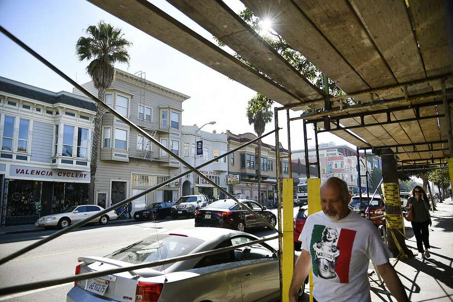 Pedestrians walk under scaffolding in front of nine units of market-rate housing under construction at 1050 Valencia St. Photo: Michael Short, Special To The Chronicle