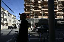Pedestrians walk past new housing construction at 3420 18th St. in the Mission District of San Francisco, CA Friday, November 6, 2015.