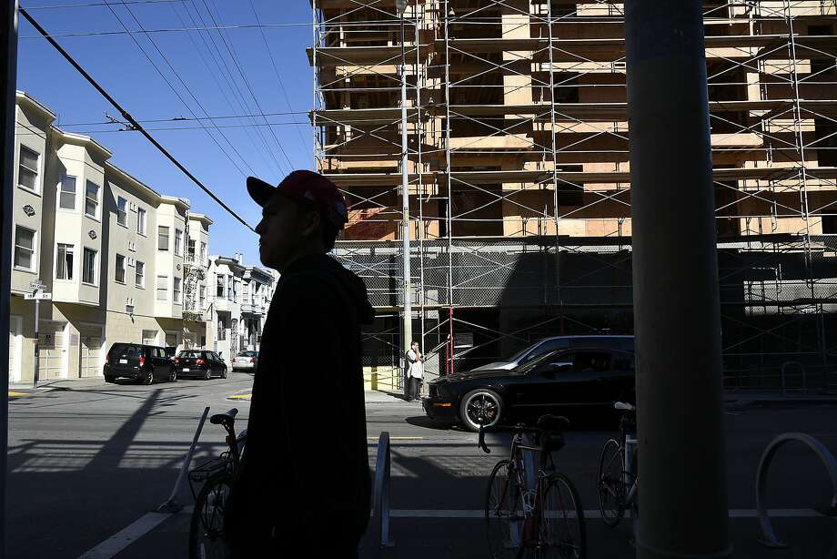Pedestrians walk past new housing construction at 3420 18th St. in the Mission District of San Francisco, CA Friday, November 6, 2015. Photo: Michael Short, Special To The Chronicle