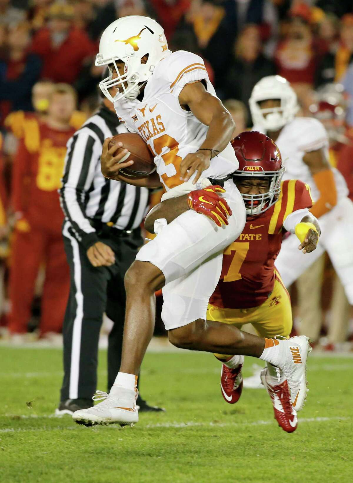 Quarterback Jerrod Heard of the Texas Longhorns is tackled by defensive back Qujuan Floyd of the Iowa State Cyclones as he scrambled for yards in the first half.