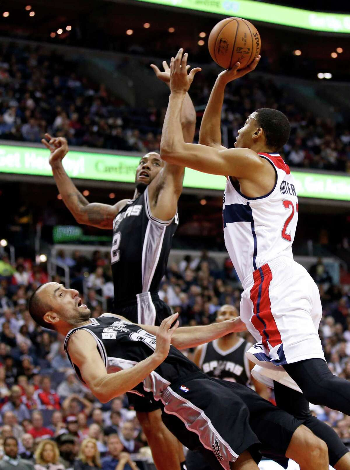 Spurs guard Manu Ginobili draws a charge from Washington Wizards forward Otto Porter Jr. with forward Kawhi Leonard nearby during the second half on Nov. 4, 2015, in Washington. The Wizards won 102-99.