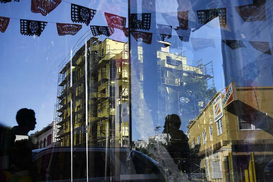 New housing construction at 1050 Valencia St. is seen reflected in a store front window displaying Dia de los Muertos items, in San Francisco, CA Friday, November 6, 2015. Photo: Michael Short, Special To The Chronicle