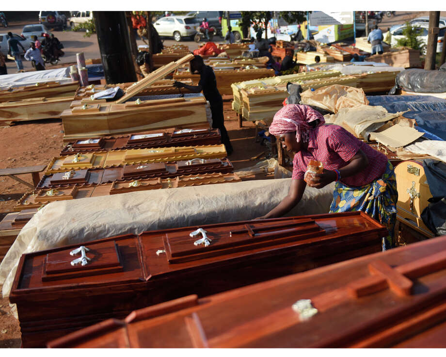 A woman puts the finishing touches of paint on a coffin, sold across the street from Mulago Hospital in the capital city of Kampala, Uganda Tuesday, July 28, 2015.  Folks construct the coffins on site in a high-traffic area directly across the street from the hospital's mortuary. Photo: Tyler Sizemore / Hearst Connecticut Media / Greenwich Time