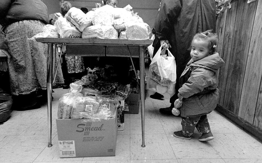 Aiesha Johnson, 2, of Stamford, waits on line with her mother and other people receiving emergency food at the Faith Tabernacle Church, 29 Grove St, on Nov. 9, 1990. More than 140 people were given groceries including peanut butter, bread and canned goods. Photo: Lucy Pemoni