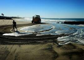 A woman jogs past a rising tide as city workers in a tractor prepare sand berms to protect the homes of local residents from flooding at Playa Del Rey Beach in Los Angeles, California on October 29, 2015.  Californian's are bracing for a super El Nino weather pattern this winter and with 20 percent of the states residents living on a flood plain, local authorities are preparing defenses against flooding and mudslides.     AFP PHOTO / MARK RALSTONMARK RALSTON/AFP/Getty Images