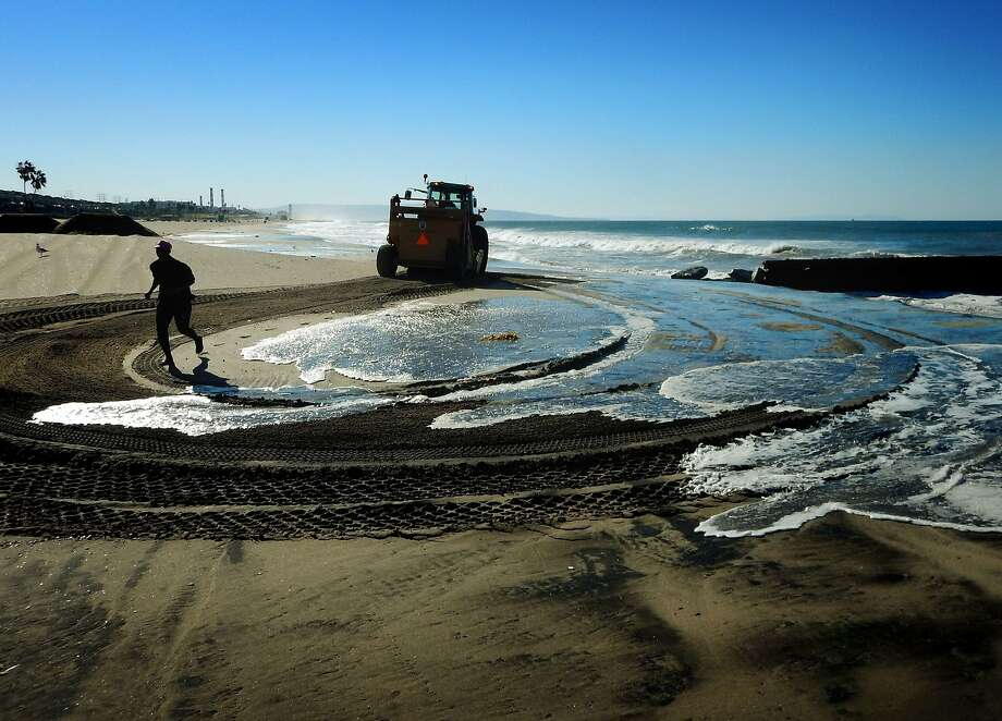 A woman jogs past a rising tide as city workers in a tractor prepare sand berms to protect the homes of residents from flooding at Playa Del Rey Beach in Los Angeles. Photo: Mark Ralston, AFP / Getty Images