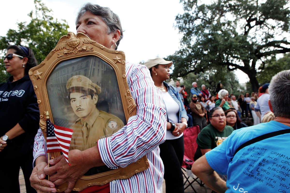 Rosie Soto Diaz holds a photo of her father, Antonio R. Soto, while watching the 2013 Veterans Parade. Her father would tell her stories about the war, she said