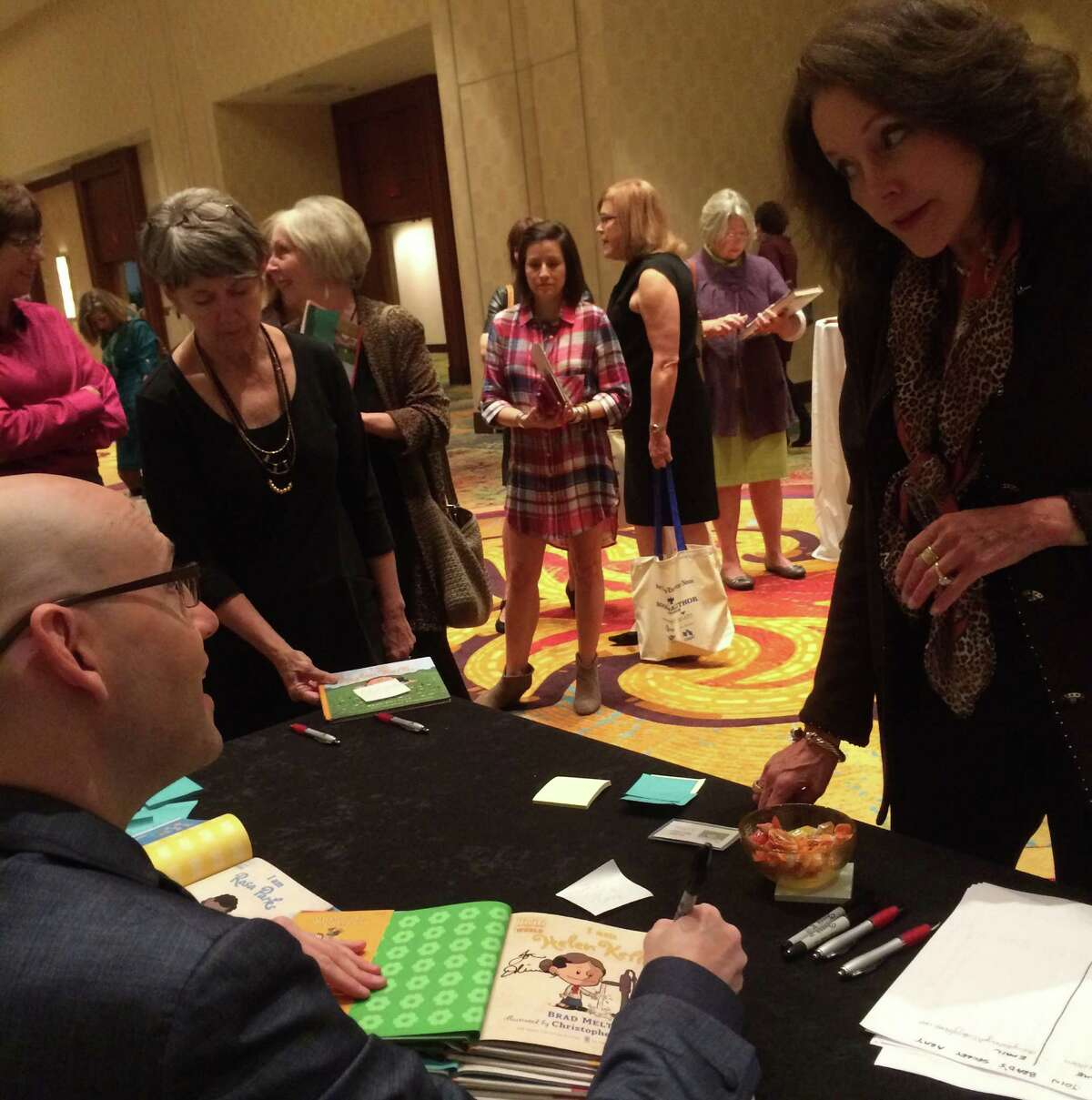 """Author Brad Meltzer, best known for his thrillers such as """"The President's Shadow,"""" signs a stack of children's books at the Express-News Book & Author Luncheon Thursday. His series of """"I am ..."""" books focus on extraordinary people who changed the world, including Heller Keller, Jackie Robinson, Amelia Earhart and Albert Einstein."""
