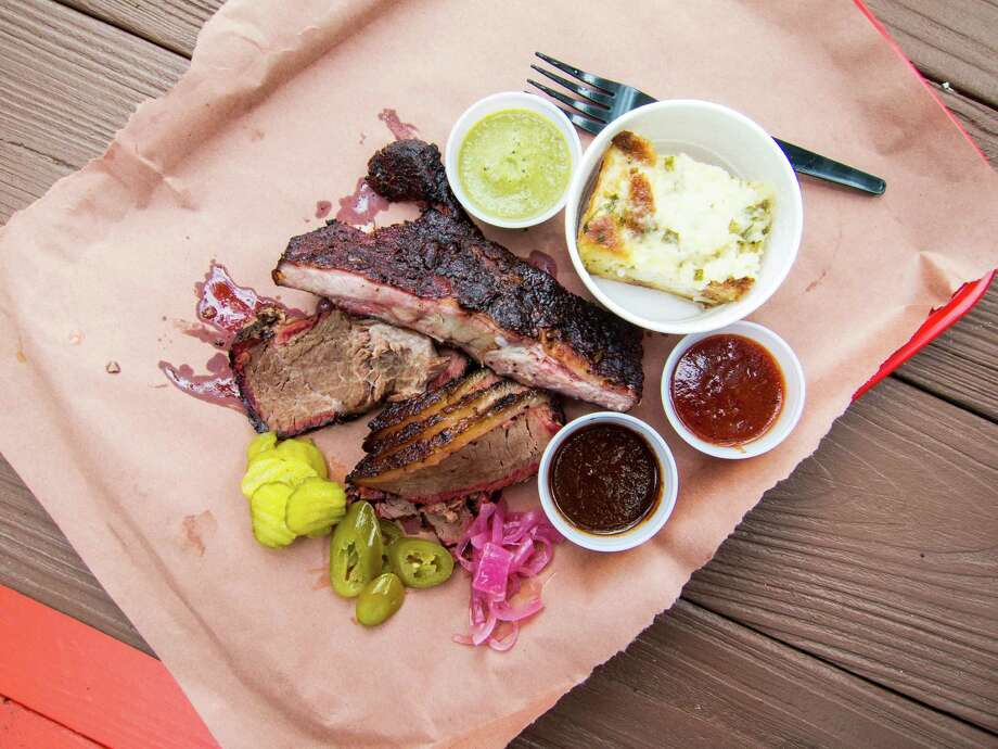 Ribs and brisket with tomato, tomatillo and mole sauces, and corn pudding at Tejas Chocolate in Tomball Photo: J.C. Reid / J.C. Reid
