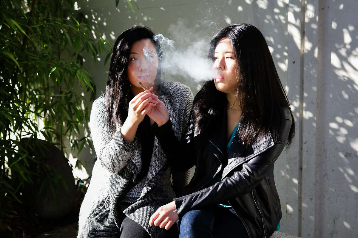 (l-r) Monica Lo and Tiffany Wu smoke a joint before work at Peace Plaza in Japantown in San Francisco, California on Friday, November 6, 2015. They are childhood friends and roommates that are working to lessen the stigma of cannabis in the Asian community.