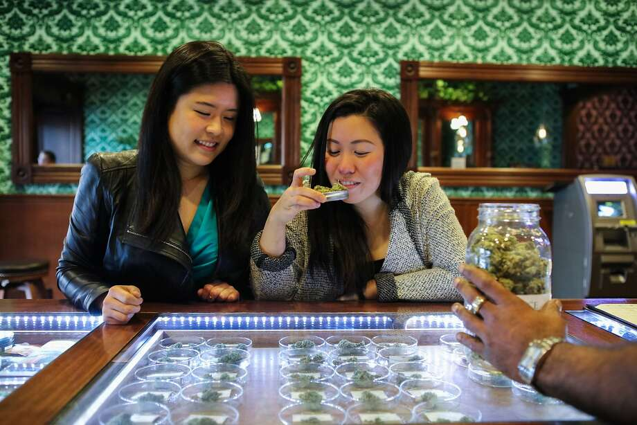 """Monica Lo (right) smells """"Bruce Banner"""" cannabis with friend and roommate Tiffany Wu (left), at their local dispensary on Post Street in San Francisco, California on Friday, November 6, 2015. The duo are childhood friends who formed an organization called AsianAmericans for Cannabis to build support among the Asian community to support legalization. Photo: Gabrielle Lurie, Special To The Chronicle"""