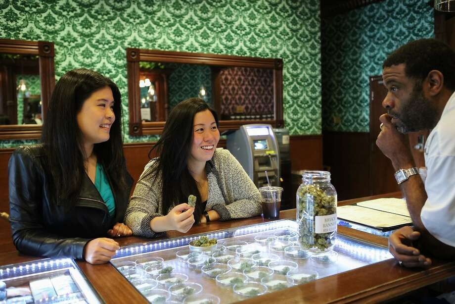 Jason Williams (right), a budtender at a dispensary in the Tenderloin, talks to Monica Lo (right) and Tiffany Wu (center) about various strands of cannabis, in San Francisco, California on Friday, November 6, 2015. Photo: Gabrielle Lurie, Special To The Chronicle