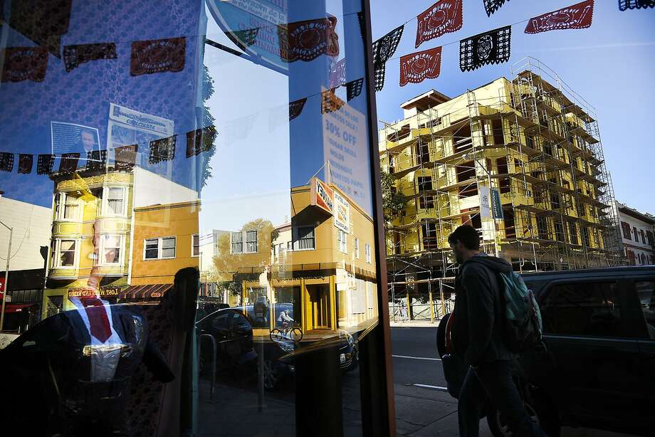 Day of the Dead flags above market-rate housing going up at 1050 Valencia are reflected in a store window. Photo: Michael Short, Special To The Chronicle