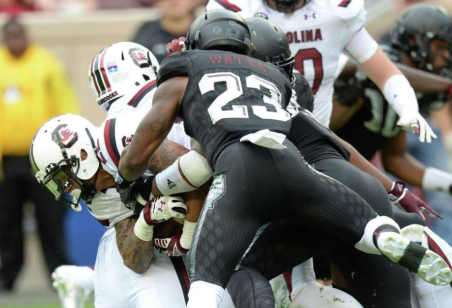 South Carolina's Brandon Wilds (22) lunges for more yards as his is tackled by Texas A&M's Myles Garrett (15) and Armani Watts (23) during the first quarter on Oct. 31, 2015 in College Station. Photo: Sam Craft /Bryan-College Station Eagle / The Bryan-College Station Eagle