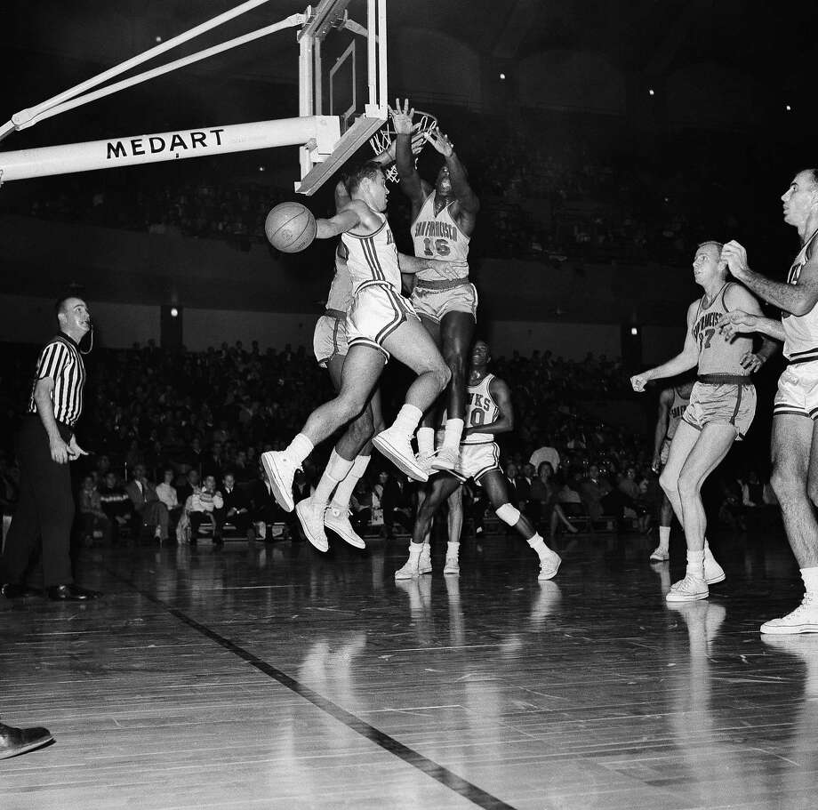 St. Louis Hawks Cliff Hagan (16) makes a high flying pass to teammate Bob Pettit after taking a shot at the basket, Jan. 6, 1963, St. Louis, Mo. With Hagan in the air is San Francisco Warrior Al Attles (16) who moved in to defend the goal. Action came during the game at Kiel Auditorium. The Hawks defeated the San Francisco Warriors 114-103. Photo: Fred Waters, ASSOCIATED PRESS