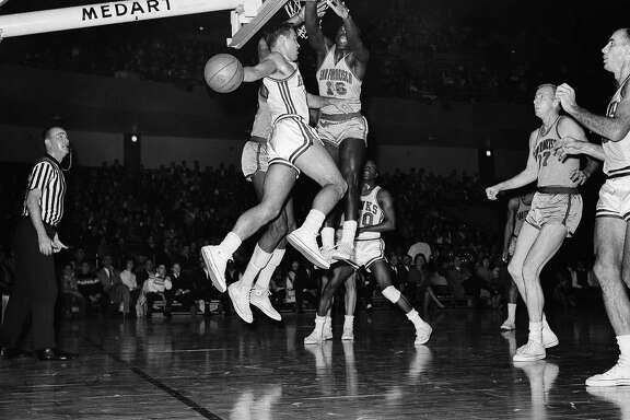 St. Louis Hawks Cliff Hagan (16) makes a high flying pass to teammate Bob Pettit after taking a shot at the basket, Jan. 6, 1963, St. Louis, Mo. With Hagan in the air is San Francisco Warrior Al Attles (16) who moved in to defend the goal. Action came during the game at Kiel Auditorium. The Hawks defeated the San Francisco Warriors 114-103. (AP Photo/Fred Waters)