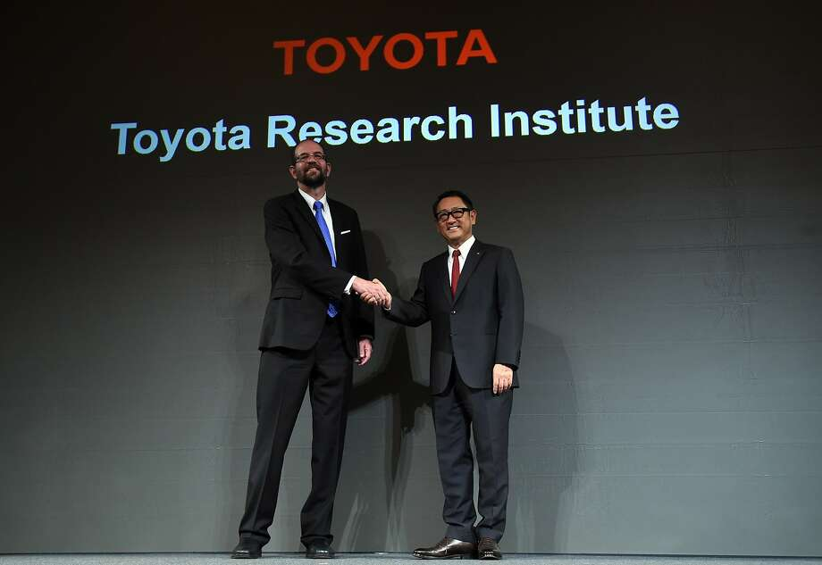Toyota Motor Corp. President Akio Toyoda (right) shakes hands with Toyota Research Institute CEO Gill Pratt. The company will have about 200 employees near Stanford. Photo: Toshifumi Kitamura, AFP / Getty Images