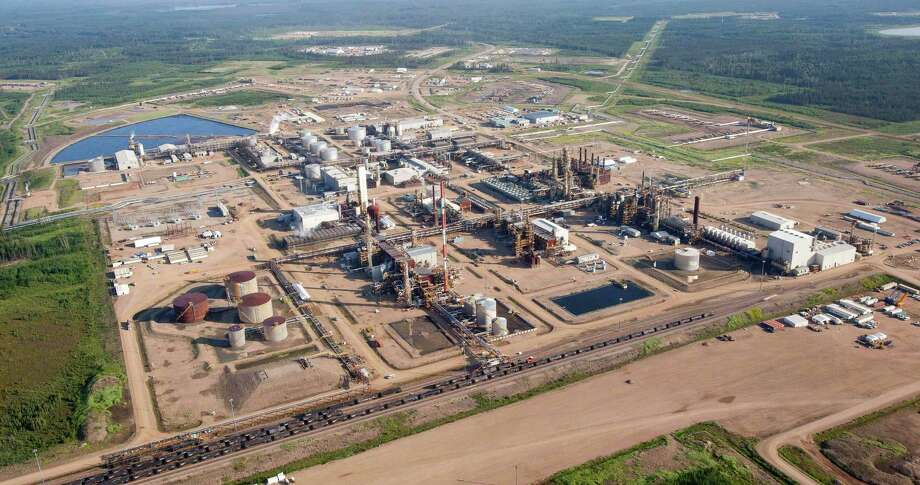 An oil sands facility operates near Fort McMurray, Alberta, Canada. The International Energy Agency estimates it costs $95 to $114 a barrel to pull crude from Canadian oil sands upgraded with high-tech extraction methods. Photo: Associated Press File Photo / The Canadian Press