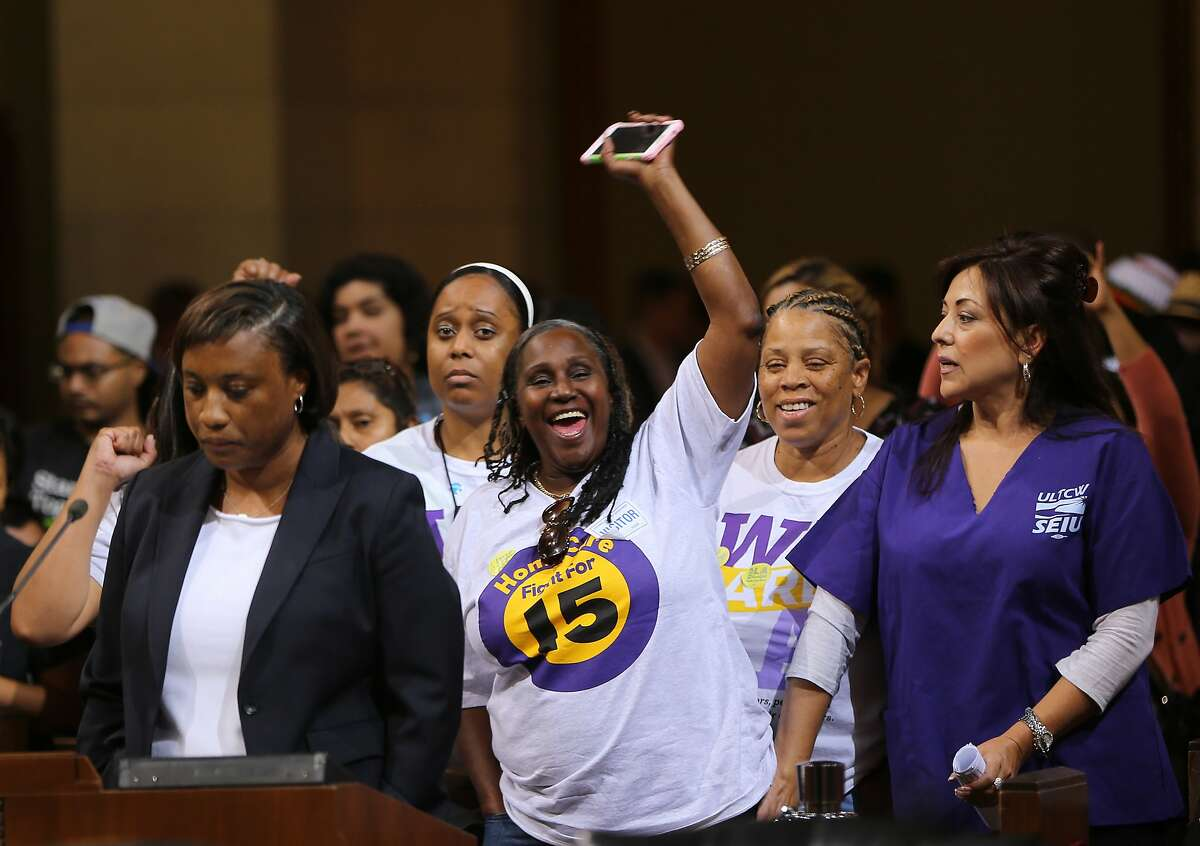 FILE - In this May 19, 2015, file photo, Laphonza Butler, President of SEIU ULTCW, the United Long Term Care Workers' Union, far left, joins workers demanding the Los Angeles City Council to vote to raise the minimum wage. The council gave initial approval to raising minimum pay in the nation's second-largest city to $15 an hour by 2020. SEIU's state council announced an initiative Tuesday, Nov. 3, 2015, that would raise the minimum wage to $15 an hour by 2020 and require at least six paid sick days a year, double the number now offered to low-wage workers. Meanwhile, SEIU's United Healthcare Workers West already has been gathering signatures for a separate measure that would raise the minimum wage by $1 an hour until it hits $15 an hour in 2021. (AP Photo/Damian Dovarganes, File)
