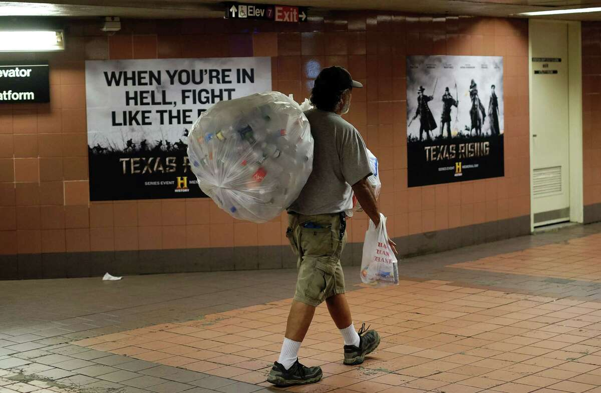 A worker  collects cans and bottles from subway stations in New York. U.S. unemployment fell to 5 percent in October.